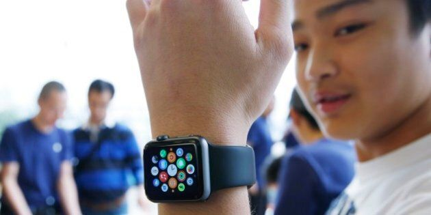 A customer tries on an Apple Watch at an Apple Store in Hong Kong Friday, April 10, 2015. From Beijing...