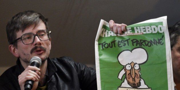 French cartoonist Renald Luzier, aka Luz, holds up the new issue of French satirical weekly Charlie Hebdo...