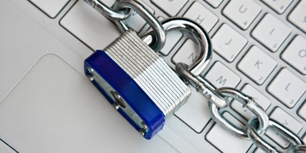 Close-up of padlock and chain around laptop computer
