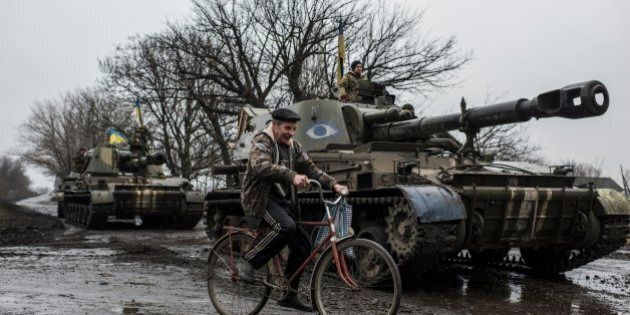 A local resident rides a bicycle as Ukrainian servicemen sit atop an armoured vehicle with Ukrainian flags, on the outskirts of Donetsk, Ukraine, Wednesday, March 4, 2015. Fighting has waned substantially in eastern Ukraine in recent days as a cease-fire deal forged last month increasingly takes effect, but both sides have complained of sporadic violations. (AP Photo/Evgeniy Maloletka)
