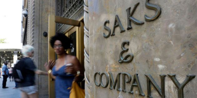 Shoppers use a Fifth Avenue entrance to Saks, in New York, Monday, July 29, 2013. Saks Inc. agreed to...