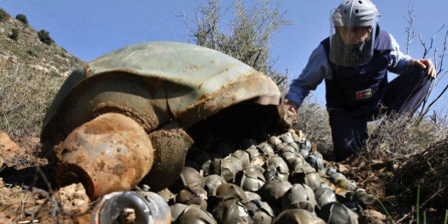 ** FILE ** In this Nov. 9, 2006 file picture, Mines Advisory Group (MAG) Technical Field Manager Nick Guest inspects a Cluster Bomb Unit in the southern village of Ouazaiyeh, Lebanon. International diplomats from more than 100 nations reached agreement on a treaty that would ban current designs of cluster bombs and require the destruction of stockpiles within eight years. The breakthrough Wednesday May 28, 2008 capped more than a year of negotiations that began in Norway and concluded over the past 10 days in Dublin, but Israel, U.S. Russia, China, India and Pakistan did not participate in the treaty. (AP Photo/Mohammed Zaatari)