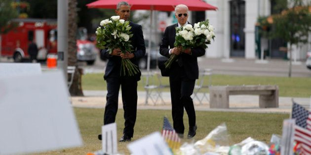 U.S. President Barack Obama (L) and Vice President Joe Biden place flowers at a makeshift memorial for...