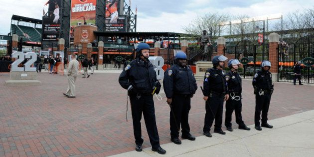 BALTIMORE, MD - APRIL 27: Police stand watch outside Oriole Park at Camden Yards before the game was...