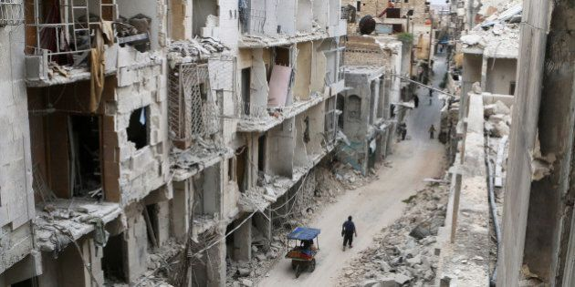 Residents walk near damaged buildings in the rebel held area of Old Aleppo, Syria May 5, 2016. REUTERS/Abdalrhman...