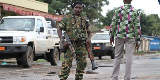A Burundian soldier with his gun and rocket launcher guard a deserted street in Bujumbura, Burundi, Sunday,...