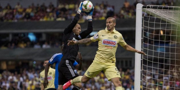 MEXICO CITY, MEXICO - APRIL 22: Dario Benedetto of America fights for the ball with Evan Bush goalkeeper...