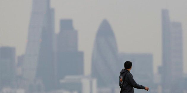 A man walks through Greenwich Park as a haze of pollution sits over the London skyline April 3, 2014....
