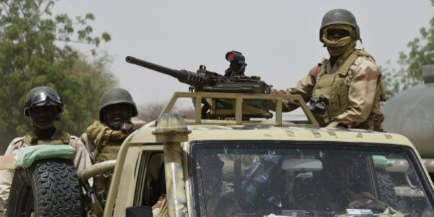 Nigerien army forces patrol in pickup trucks near Malam Fatori on April 3, 2015, after the town in north-eastern...