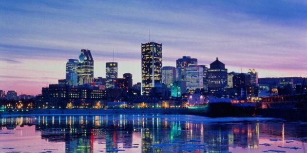 Canada,Quebec,Montreal view of city skyline reflected in river at dusk