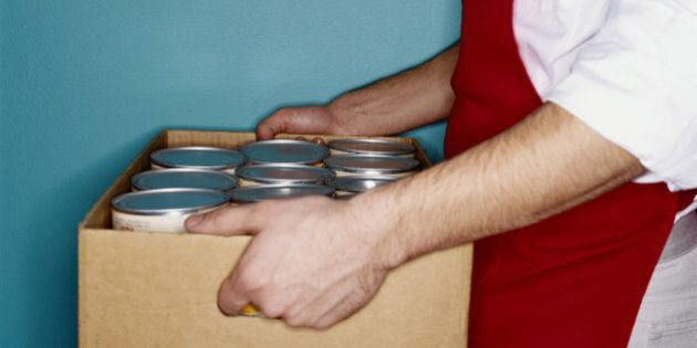 Clerk carrying box of canned goods, mid section, side