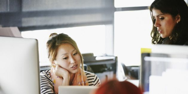 Two businesswomen in discussion at desk in high tech startup