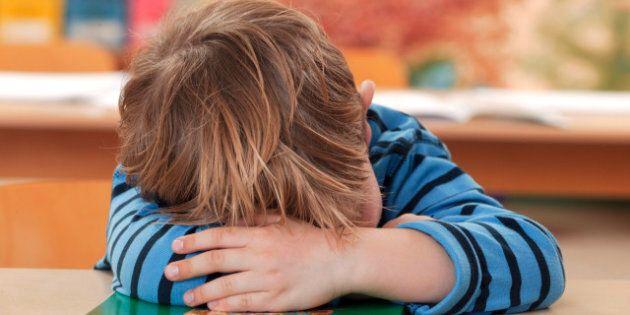 Schoolboy in stripy shirt sleeping, head resting on