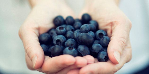 A woman offers blueberries