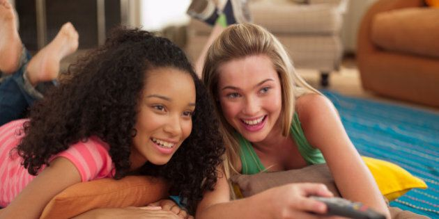 Two teenage girls lying down watching television with remote control