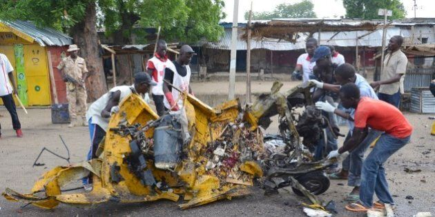 People inspect a damaged tricycle at the site of a bomb explosion in Maiduguri, Nigeria, Friday, July...