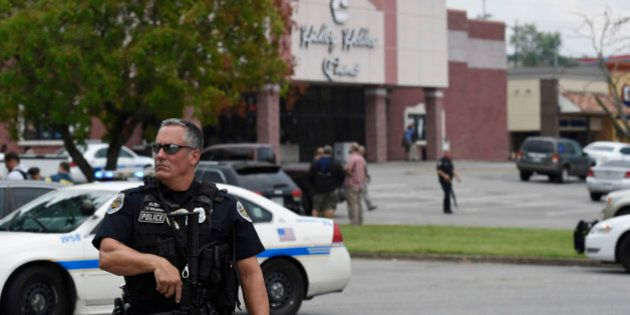 An officer stands in front of the Carmike Hickory 8 movie theater following a shooting Wednesday, Aug....