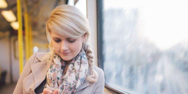 Woman using smart phone in metro.