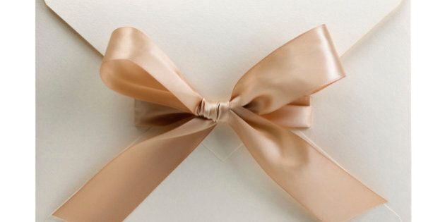 White envelope with bow, containing a wedding invitation. This is a macro photograph and its frame is square.