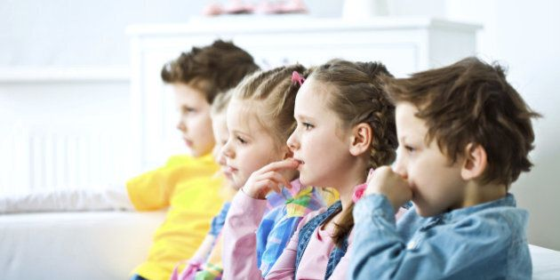 Side view on five cute kids sitting on sofa in domestic room and watching TV with interest. Focus on the girl keeping her finger in mouth.