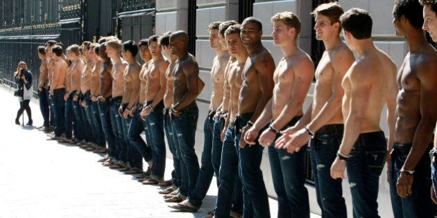 Bare-chested models pose in front of the Abercrombie & Fitch shop on the Champs Elysees in Paris Thursday May 12, 2011, as  of the promotion of the  opening of the new U.S. brand shop in Paris.(AP Photo/Remy de la Mauviniere)