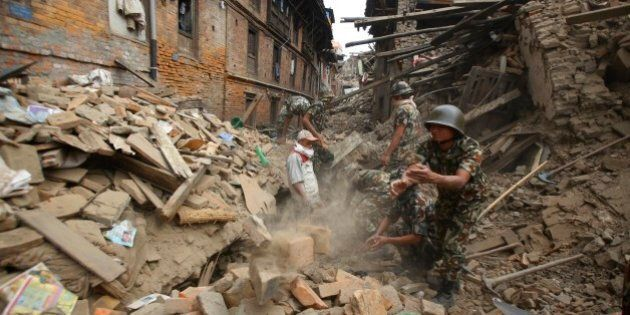 Rescue workers remove debris as they search for victims of earthquake in Bhaktapur near Kathmandu, Nepal,...