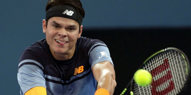 Milos Raonic of Canada plays a shot in his semifinal game against Bernard Tomic of Australia during the...