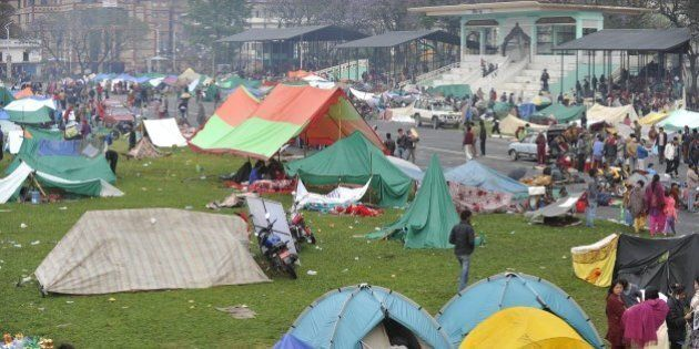 Nepalese people gather near temporary shelters set up in open areas of an Army ground in Kathmandu on...