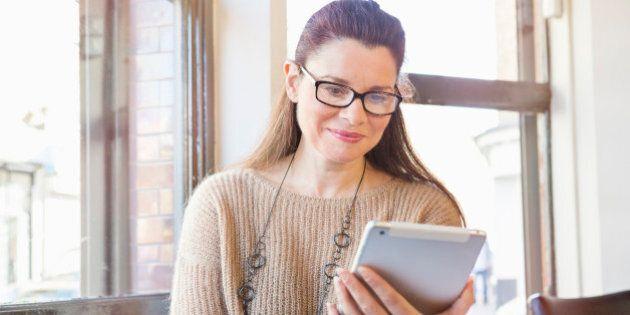 Senior woman working on digital tablet in