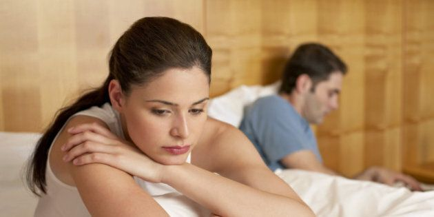 Bored woman sitting in bed with man using laptop by