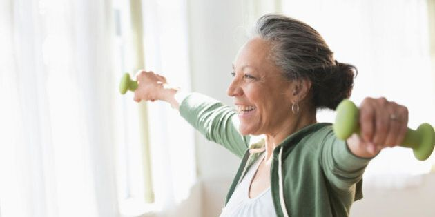 Older Hispanic woman lifting weights in living