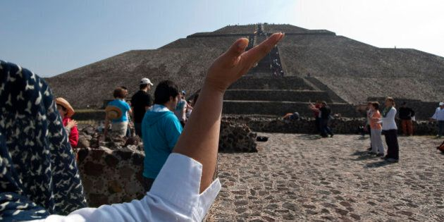 A tourist raises her hands to the sun to take its energy in front of the Pyramid of Sun in Teotihuacan...