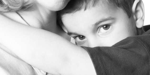 Mother holding shy son