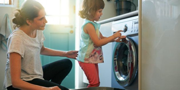 Shot of a mother and daughter using a washing machine