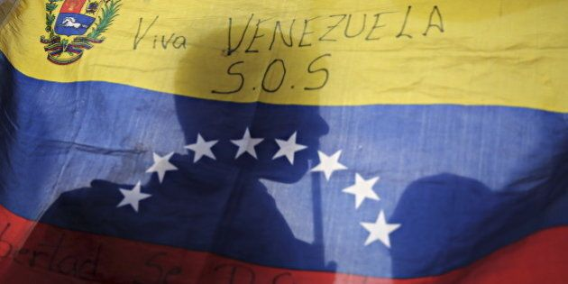 Opposition supporters are silhouetted through a Venezuelan flag during a campaign rally with candidates...