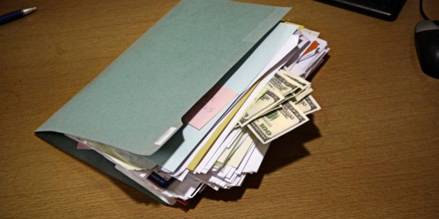 folder on desk with 100 dollars bills stuck in