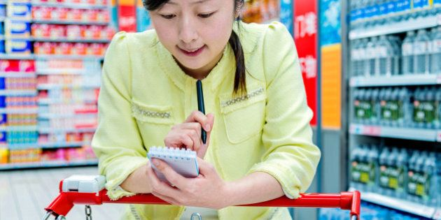 Asian attractive woman holding shopping list in a