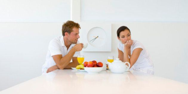 Woman ignoring man during breakfast