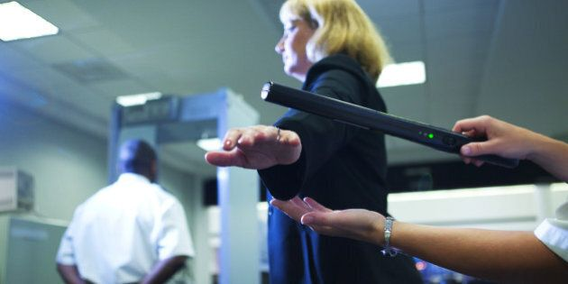 Close-up of an airport security officer using a hand held metal detector to check a