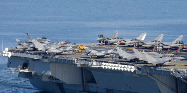 War planes are on the deck of France's nuclear-powered aircraft carrier Charles de Gaulle as it eaves...