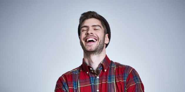 Portrait of young bearded man with tattooed arms in red and blue check shirt and beanie, laughing with...