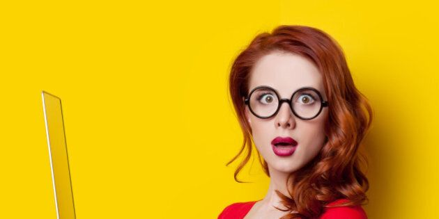 Surprised redhead girl with laptop computer in red dress on yellow