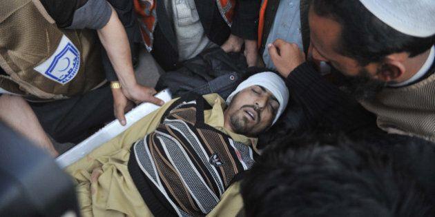 Pakistani paramedics transport a bomb blast victim to a hospital in Peshawar on December 29, 2015. At...
