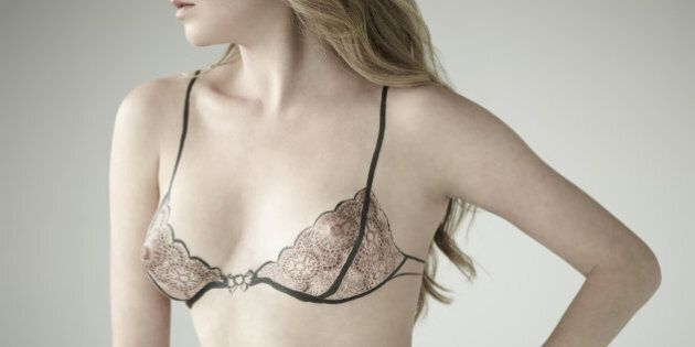 portrait of young woman with black marker drawing of bra on her body drawn over her