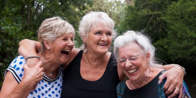 Three elderly women holding one another and laughing out loud, outdoors in a green environment on an...