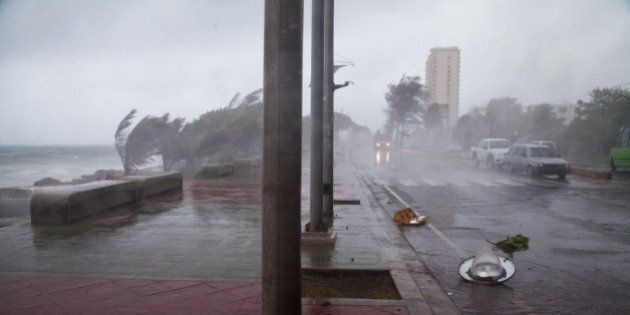 Broken traffic lights and street lamps lay on the ground as the strong winds of Tropical Storm Erika...