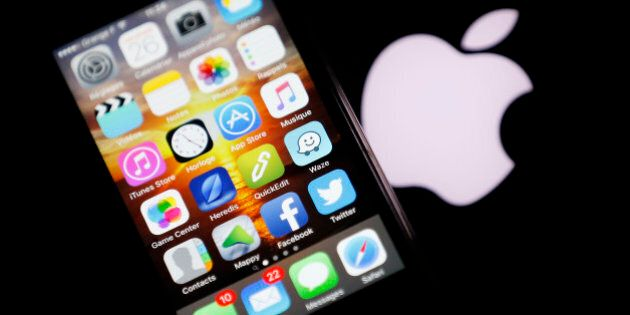 An Apple iPhone is pictured next to the logo of Apple in Bordeaux, southwestern France, February 26,...