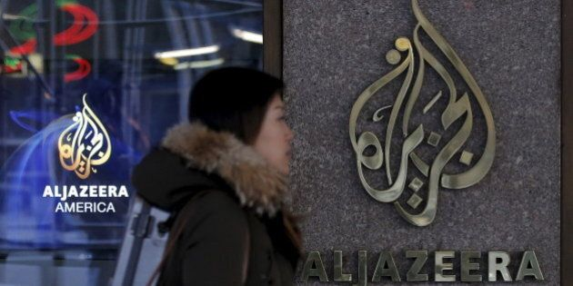 A woman passes by the Al Jazeera America broadcast center in midtown Manhattan in New York City January 13, 2016. Al Jazeera America, the cable television news outlet owned by Qatar-based Al Jazeera Media Network, is shutting down less than three years after its high-profile launch, the network said on Wednesday. REUTERS/Brendan McDermid       TPX IMAGES OF THE DAY