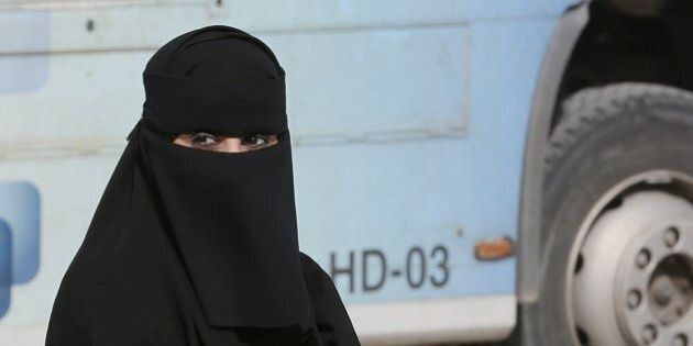 A Saudi woman waits outside a polling center as she prepares to cast her ballot during the country's...