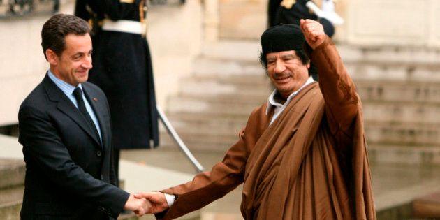 France's President Nicolas Sarkozy (L) greets Libyan leader Muammar Gaddafi in the courtyard of the Elysee...